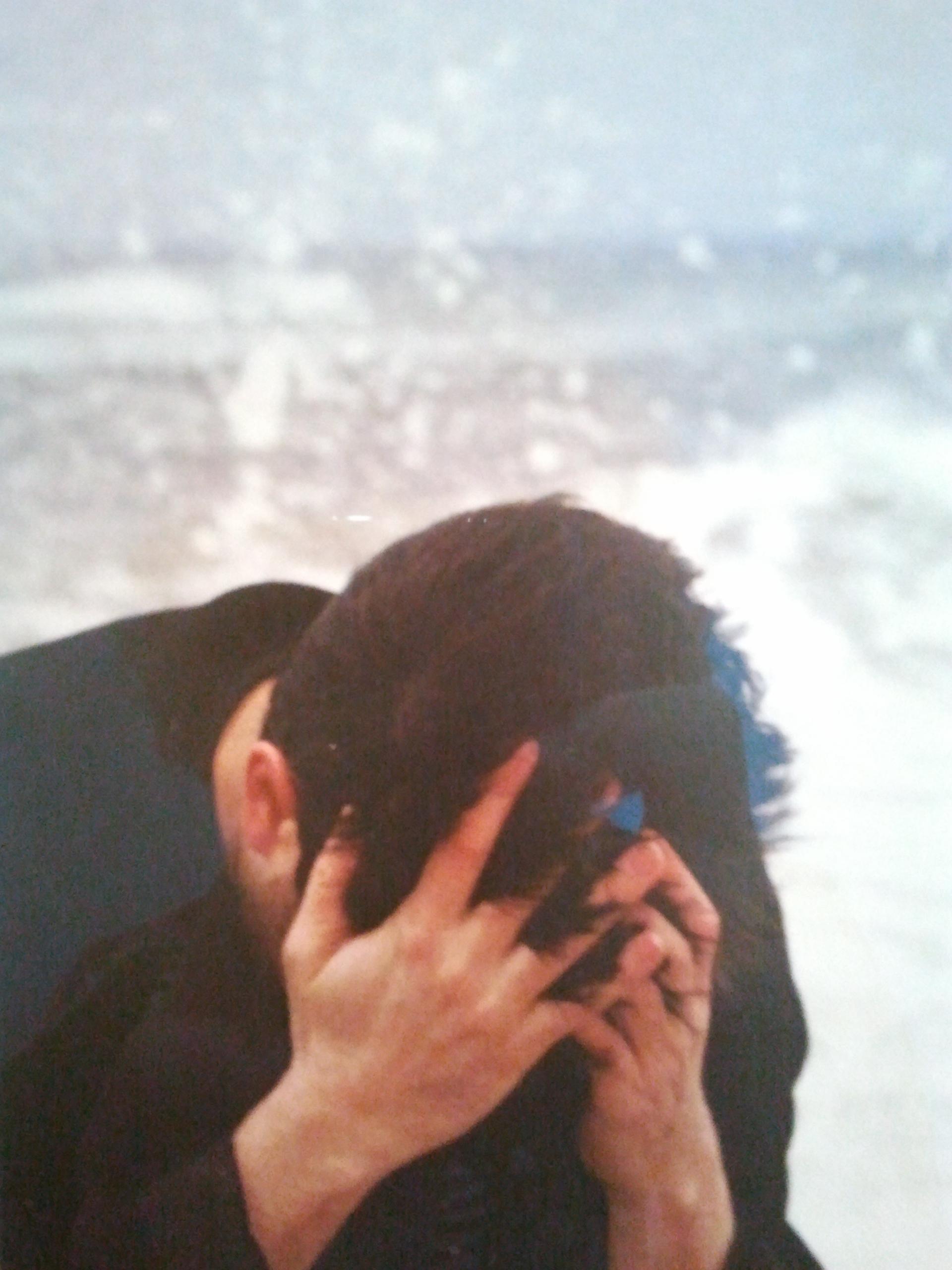 Un homme se tient la tête entre les mains dans un geste de détresse représente l' Anxiété généralisée, bleu